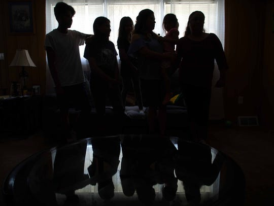The family of Jose Santillan, who was taken into custody by ICE, reflected in the coffee table of his home.