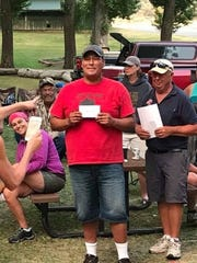 Mitchell Healy displays an envelop with his prize winnings and a nameplate saying he is the 2018 Montana state horseshoe tournament champion.