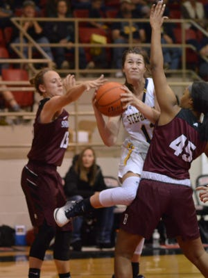 Stephenille's Jayci Morton (12) drives between Brownwood defenders Ryleigh Dalleh (15) and Tyanne Stewart (45) in the third quarter of Friday's 4A area round game in Hamilton.