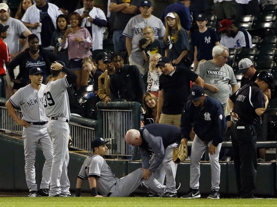 Yankees right fielder Dustin Fowler is checked by trainer Steve Donohue after an injury in the first inning of the team's game against the White Sox on Thursday, June 29, 2017, in Chicago.