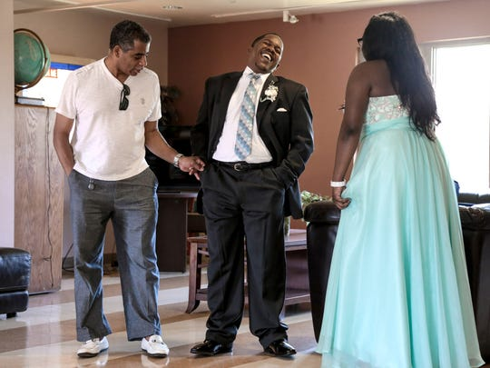 Covenant House Michigan resident advisor Kevin Lomax (left) shows Joshua Sims, 21, how to pose for a photo as Sims meets up with his prom date Covenant House Michigan resident Siani Williams, 21, at Covenant House Michigan in Detroit on Thursday June 8, 2017.