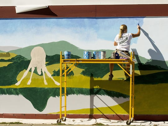 Mary Beth Ihnken blends paint together to create the sky of her 2007 mural on the wall of the Unfinished Furniture Store on Taughannock Boulevard in Ithaca's West End.
