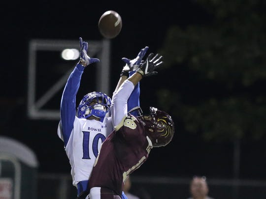 Bowie receiver Dominic Johnson catches a pass over Andress defender Antonio Gomez Friday night at Andress High School.