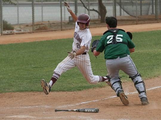 Ryan Rodriguez of Rancho Mirage is tagged out by Twentynine Palms catcher Casey Allen during the Rattlers win over the Wildcats, May 9, 2017.