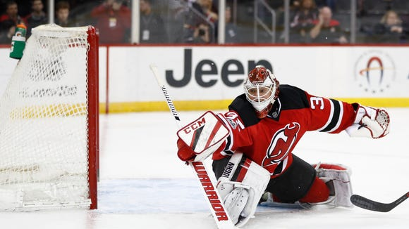 New Jersey Devils goalie Cory Schneider deflects a shot from the Carolina Hurricanes during the first period of an NHL hockey game, Saturday, March 25, 2017, in Newark, N.J. (AP Photo/Julio Cortez)