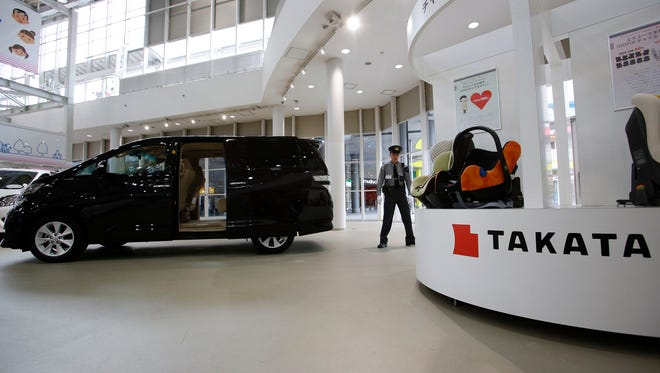 In this Nov. 6, 2014 file photo, a security guard stands by child seats, manufactured and displayed by Takata Corp. at a Toyota showroom in Tokyo.