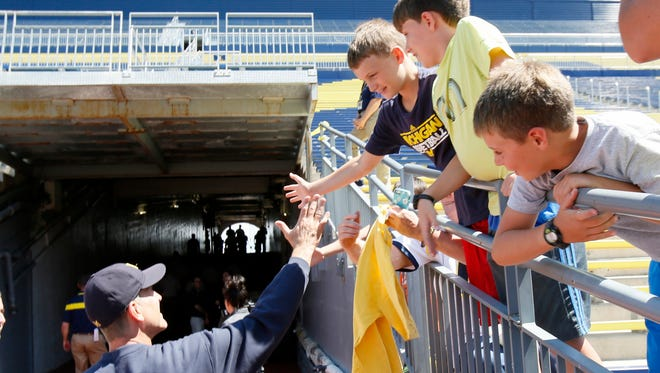 Michigan football coach Jim Harbaugh greets fans as he leaves the field after the team's official photo at Michigan Stadium on Aug. 6, 2015, in Ann Arbor.