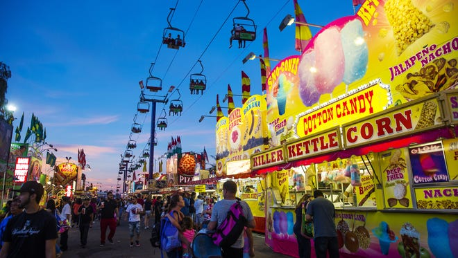 Visitors at the Arizona State Fair walk under the Sky Ride October 16, 2016.