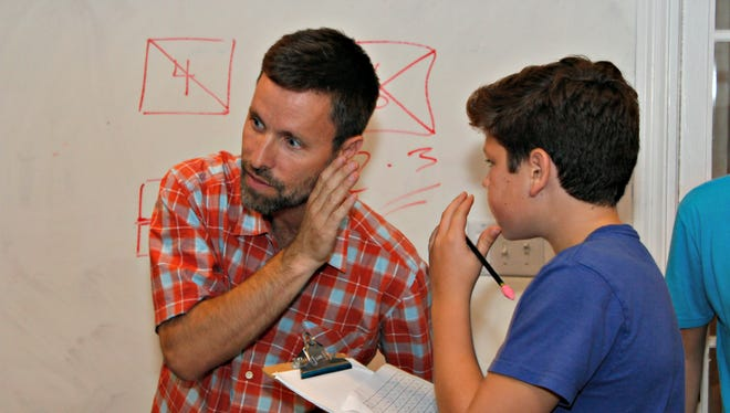 Seth Harte, 13, a seventh-grader at Edmunds Middle School, whispers an answer to Burlington parent Jeff Wick during a math session on Oct. 5. Wick teaches students at his home one night per week to fulfill a gap he sees in advanced learning opportunities in the Burlington School District.
