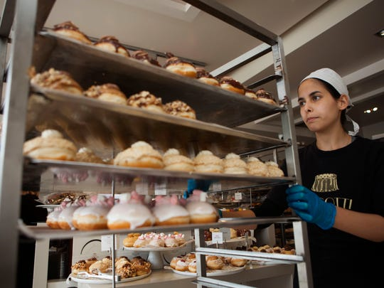 In this Thursday, Dec. 15, 2016 photo, a bakery employee wheels doughnuts in Bnei Brak, Israel. Israelis are finding new advice hard to swallow: in the name of proper nutrition, their health minister has gone on the warpath against the beloved Hanukkah tradition of gorging on sugar-laden, deep-fried, jam-filled doughnuts. Yaakov Litzman _ the bearded, black-coated chief of a powerful ultra-Orthodox political party _ considers himself a guardian of Jewish traditions. But he also wears another hat, as a health conscious official on a crusade to stamp out junk food and child obesity.