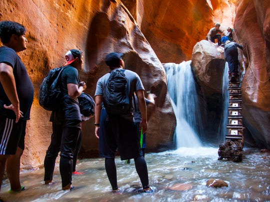 A group of friends wait at the bottom of the Kanarraville Falls while another group comes down the ladder, June 6, 2017.
