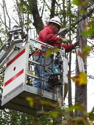 """Jeff West, 52, a lineman at Verizon from Hyde Park, conducts a """"transfer"""" on Ann Street in the Town of Poughkeepsie."""