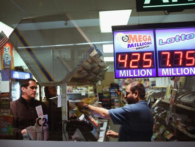 CHICAGO, IL - DECEMBER 13:  A clerk sells Mega Millions lottery tickets at a convenience store on December 13, 2013 in Chicago, Illinois. Tonight's Mega Millions jackpot will be an estimated $425 million, the second-largest jackpot in the history of the game.  (Photo by Scott Olson/Getty Images)