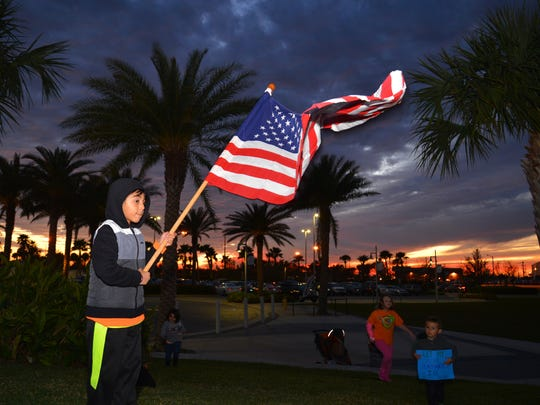 Mishary Alqawasmi, 7, waves an American flag while speakers talk to the crowd. Protesters gather Sunday evening at Exploration Tower in Port Canaveral to protest Donald Trump's immigration order.