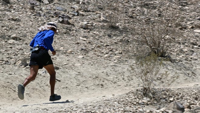 Hikers frequent the Mike Schuler Trail leading to the Bump and Grind Trail, where a man died Saturday in Palm Desert. This trail runner is among those who are still hiking the trail amid the desert's triple-digit heat.