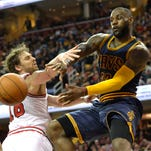 Cleveland Cavaliers forward LeBron James (23) passes around Chicago Bulls forward Pau Gasol (16) and center Joakim Noah (13) in the third quarter at Quicken Loans Arena. James had a triple-double in the Cavaliers 99-94 win.