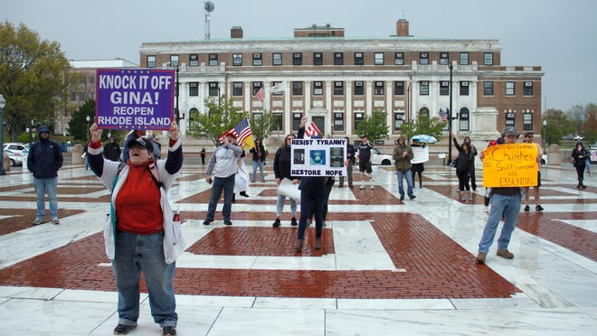 Signs of frustration abound at the Rhode Island State House on May 11 as protesters call on Gov. Gina Raimondo to lift coronavirus restrictions.