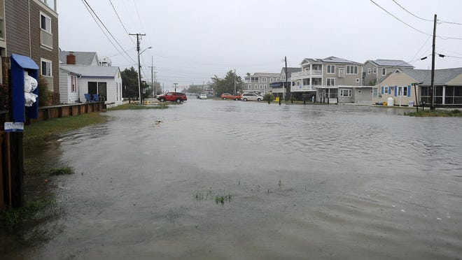 Sea-level rise will worsen the impact of storm surges on coastal communities, bringing more frequent flooding like this October washout along Read Street in Dewey Beach four years ago.