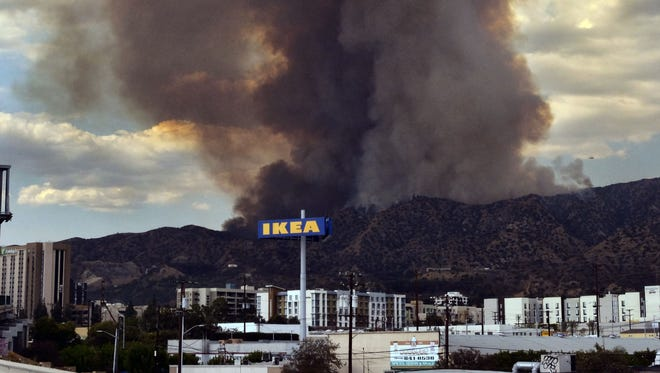 Heavy black smoke rises as a wildfire burns in Los Angeles