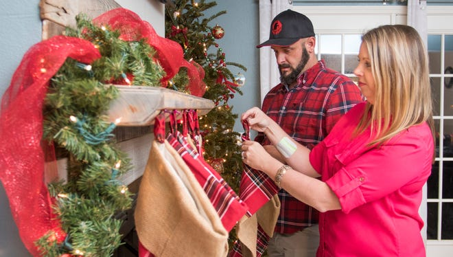 Marine veteran James Vassaur and his wife Lindsay hang stockings above the fireplace as they get ready for Christmas at their home in Pensacola on Monday, December 19, 2016.