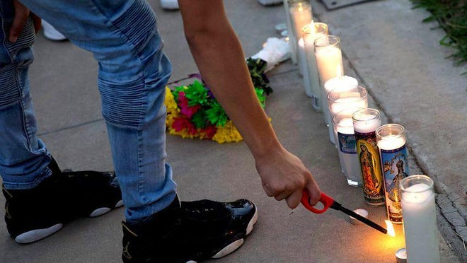 A person attending a vigil for Leilah Hernandez, one of the victims of the mass shooting in Odessa and Midland, lights a candle on Sept. 2, 2019.