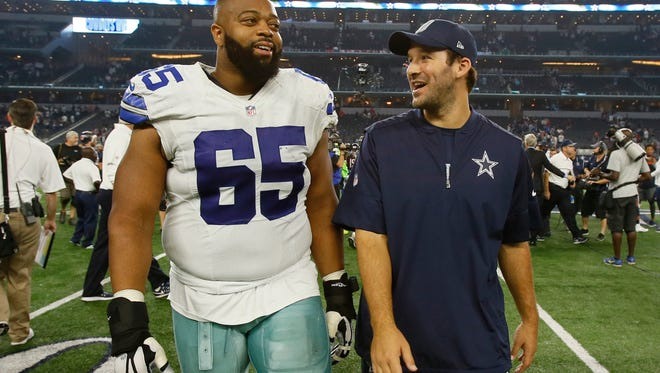 Dallas Cowboys guard Ronald Leary (65) and Dallas Cowboys quarterback Tony Romo (R) leaves the field after the game against the Chicago Bears at AT&T Stadium. Dallas won 31-17.