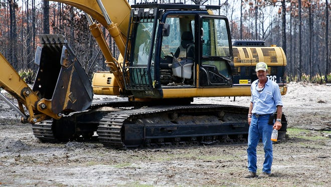 Tallahassee utility worker Mike Hunter steps out of his excavator for a moment during clean up on Ridge Road in Eastpoint on Monday. Hunter is one of the 15 crews men sent to clear the debris from the Eastpoint community that was destroyed by a wildfire on June 24th.