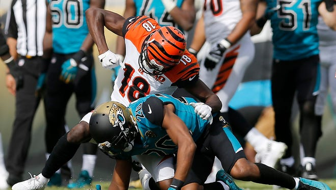 Cincinnati Bengals wide receiver A.J. Green (18) throws a punch at the helmet of Jacksonville Jaguars cornerback Jalen Ramsey (20) after pulling him to the ground after a play in the second quarter at EverBank Field.