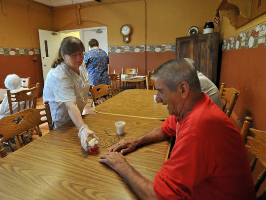 Barb Glass, left, serves Fairview Assisted Living resident Paul W. Hutchison Jell-O and coffee Tuesday morning, Aug. 12, 2014, at the facility in New Lexington. Fairview Assisted Living is one of fewer than 30 county homes still in operation in Ohio.