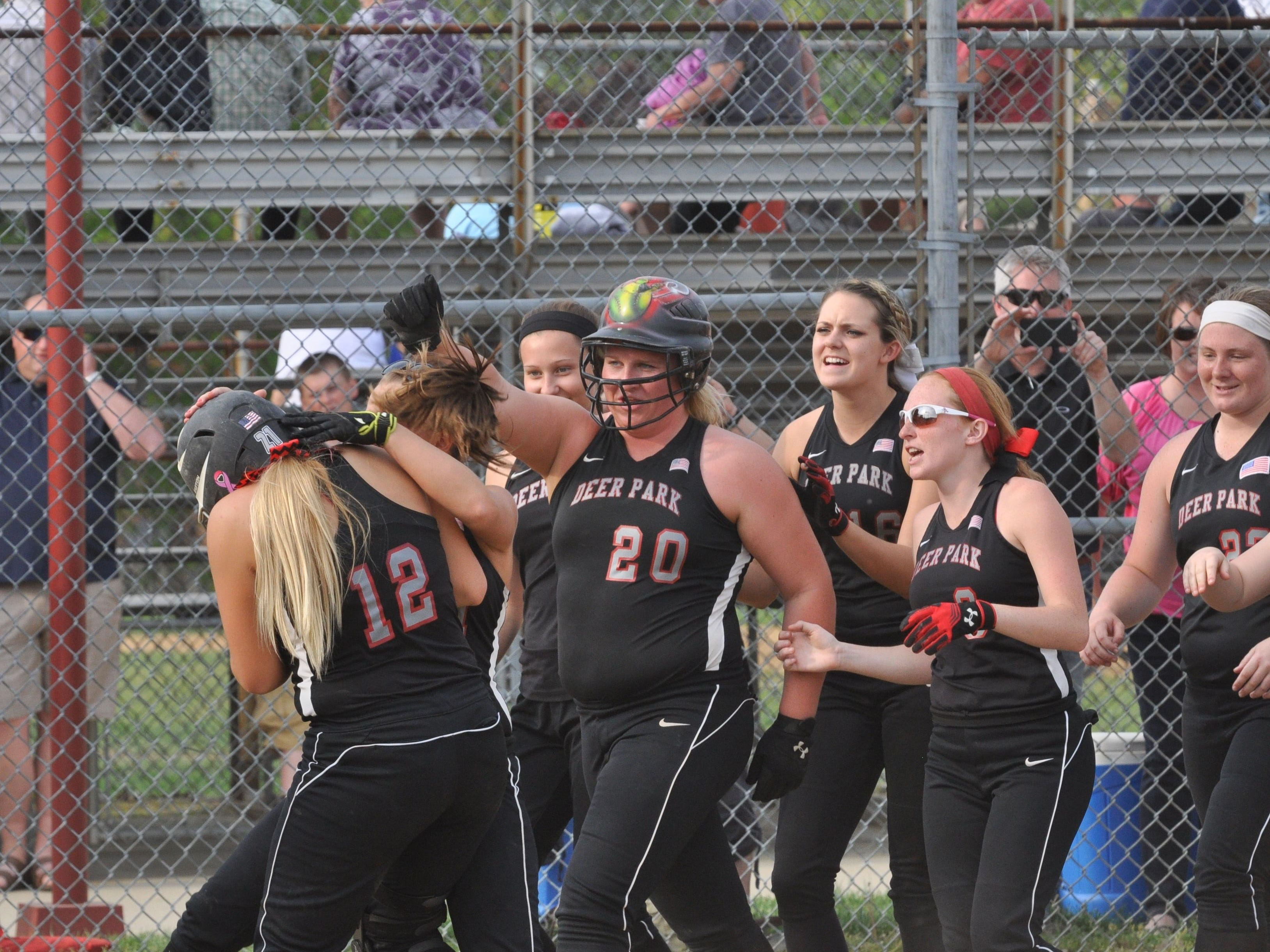 The Lady Wildcats of Deer Park celebrate a home run over their new fence donated by Bobby Castrucci.
