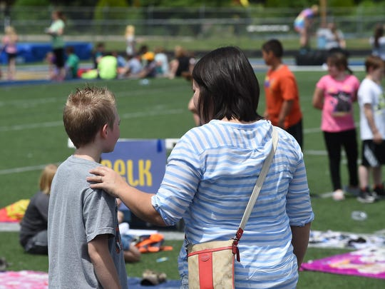 """Sarah Reynolds talks with her son at a recent school event at Bomber Stadium. """"He's not ashamed of us — he's not embarrassed of us — but that's my fear that society and the people around him are going to make him that way,"""" Sarah said."""