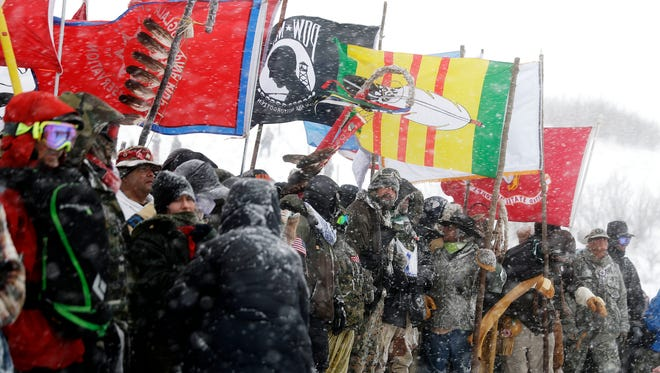 In this Dec. 5, 2016, file photo, military veterans and Native American tribal elders come to a stop for a ceremonial prayer during a march to a closed bridge across from the Dakota Access oil pipeline site in Cannon Ball, N.D.