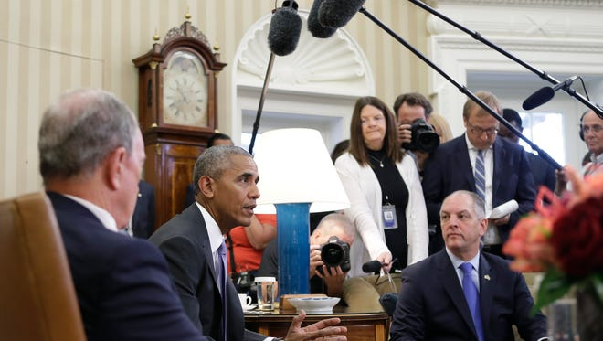 President Barack Obama, joined by former New York City Mayor Michael Bloomberg, left, and Louisiana Gov. John Bel Edwards, right, talks to media at the start of a meeting with business, government, and national security leaders in the Oval Office of the White House in Washington, Friday, Sept. 16, 2016, to discuss how the Trans-Pacific Partnership can benefit American workers and businesses and further national security. (AP Photo/Carolyn Kaster)