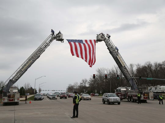 Members of the Des Moines Fire Department hang a large american flag for Des Moines Police Officer Susan Farrell's funeral procession to pass under on Wednesday, March 30, 2016, outside of Hope Lutheran Church in West Des Moines.