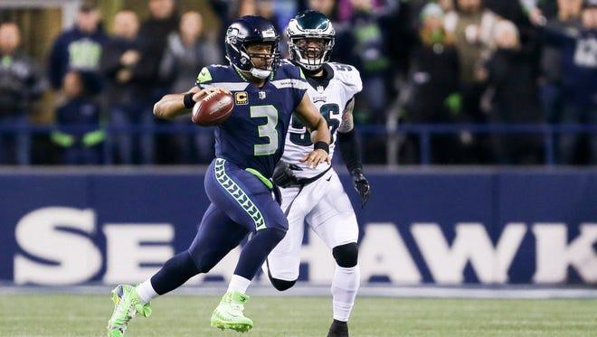 Seattle Seahawks quarterback Russell Wilson (3) scrambles against Philadelphia Eagles defensive end Chris Long (56) during the second quarter at CenturyLink Field.