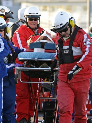 Rescue workers move driver Memo Gidley to an ambulance for transport to the hospital.