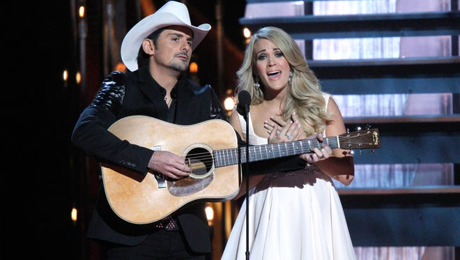 Hosts Brad Paisley, left, and Carrie Underwood perform on stage at the 48th annual CMA Awards at the Bridgestone Arena on Wednesday, Nov. 5, 2014, in Nashville, Tenn. (Photo by Wade Payne/Invision/AP) ORG XMIT: TNBR203