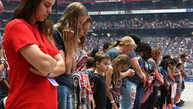 "Attendees of Harvest America 2017 bow their heads in prayer. Taking place at University of Phoenix Stadium, the event has been billed ""the nation's largest one-day evangelistic outreach."" Attendance reached 38,000."