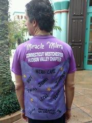 "William Hiemcke poses with his Miracle Milers ""Hero Cape he wore through the half-marathon and marathon races at Disney World."