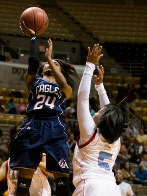 Montgomery Academy's Jade Brooks shoots over Midfield's Kierra Hicks during the AHSAA Class 3A Central Regional championship on Thursday at the Acadome.