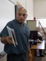 Christopher Ramirez practices reading aloud a story about the biblical parable of The Good Samaritan in a classroom at Kettle Moraine Correctional Institution on Wednesday, July 15, as his instructor, Mary Pohlman, looks on. Ramirez completed the prison's For the Love of Reading Program that is meant to encourage early literacy skills.