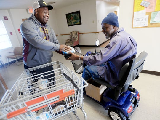 John Clay gives food to Lee Patrick, a 64-year-old