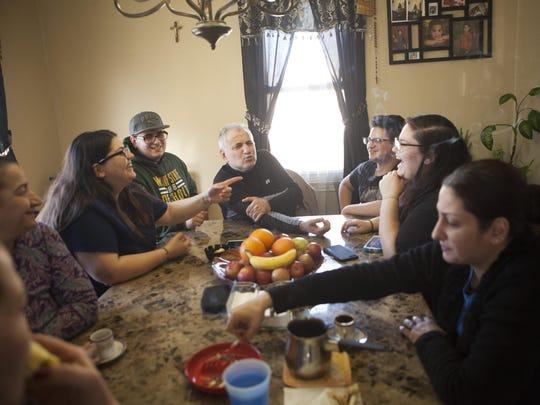Warda Slewo, center, sits with family and friends Friday