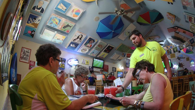 Janet Cook, Sue Stewart and Diana Aulizia peruse the menu at the Sanibel Fish House while bartender Jake Marsh brings them strawberry lemonade Tuesday on Sanibel Island. The eatery's ceilings feature decorative noise-reducing acoustic  tiles.