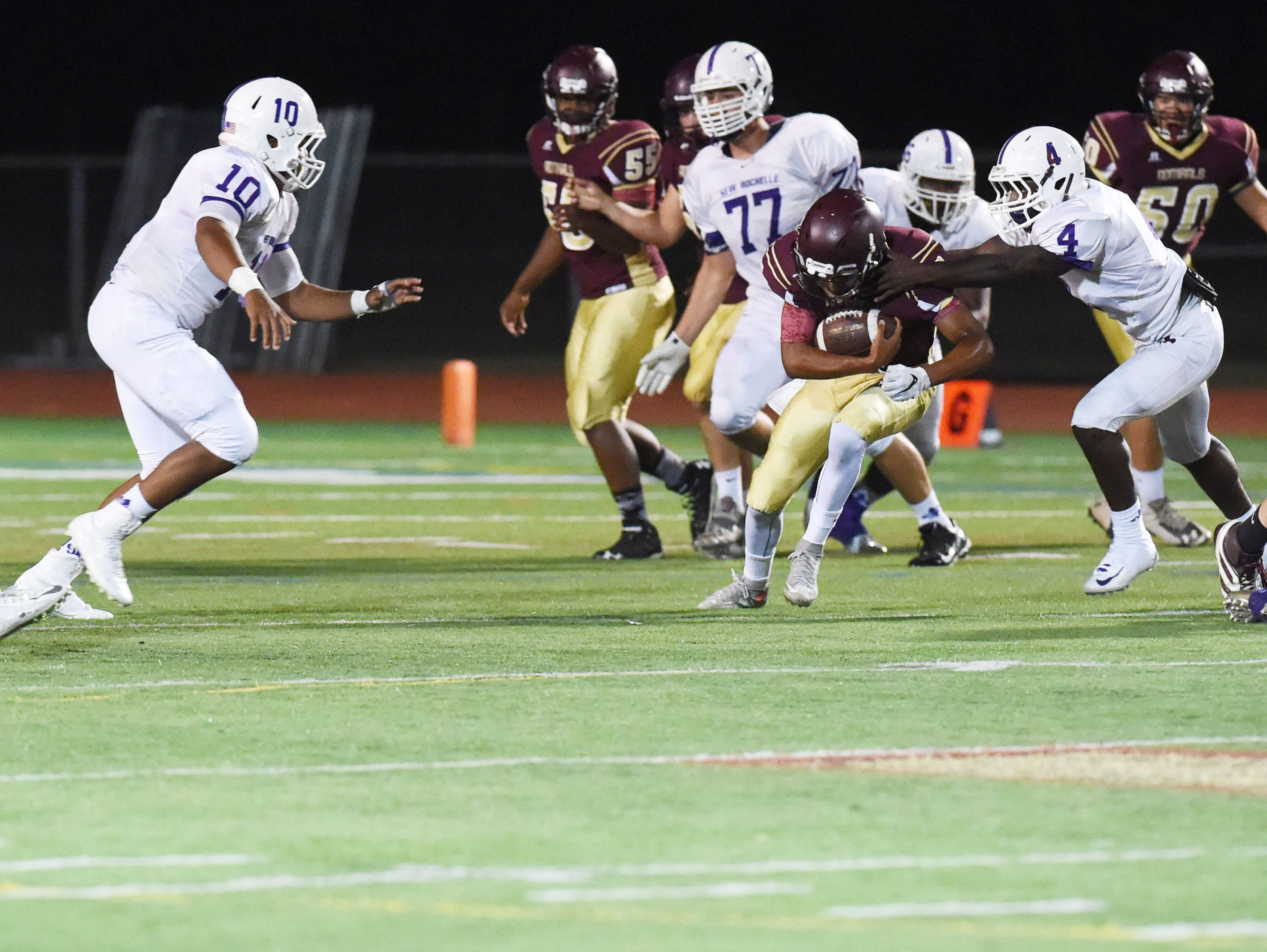 Arlington's Justin Leigh charges through a hole as New Rochelle's Jonathan Saddler, left, and Keelan Thomas, right, defend.
