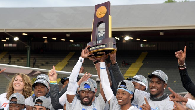 Eric Futch and Florida teammates hold the championship trophy after the Gators won the men's team title during the NCAA Track and Field Championships.