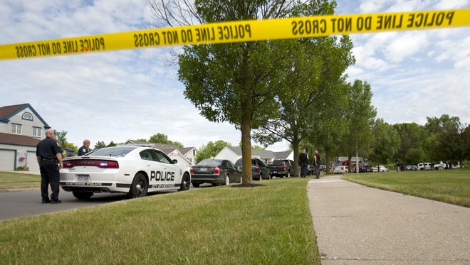 Authorities respond to the scene near where police shot and killed an armed bank robbery suspect in Grand Rapids on June 13, 2016.