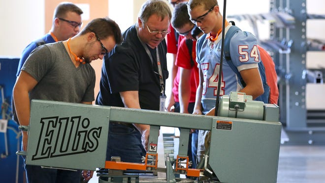 Manufacturing instructor Jerry Torresdal, center, speaks with Spencer Christian, right, a junior at South Salem, and Joe Glascock, a senior at North Salem, about an Ellis bandsaw at the recently opened Career and Technical Education Center, Thursday, September 10, 2015, in Salem, Ore.