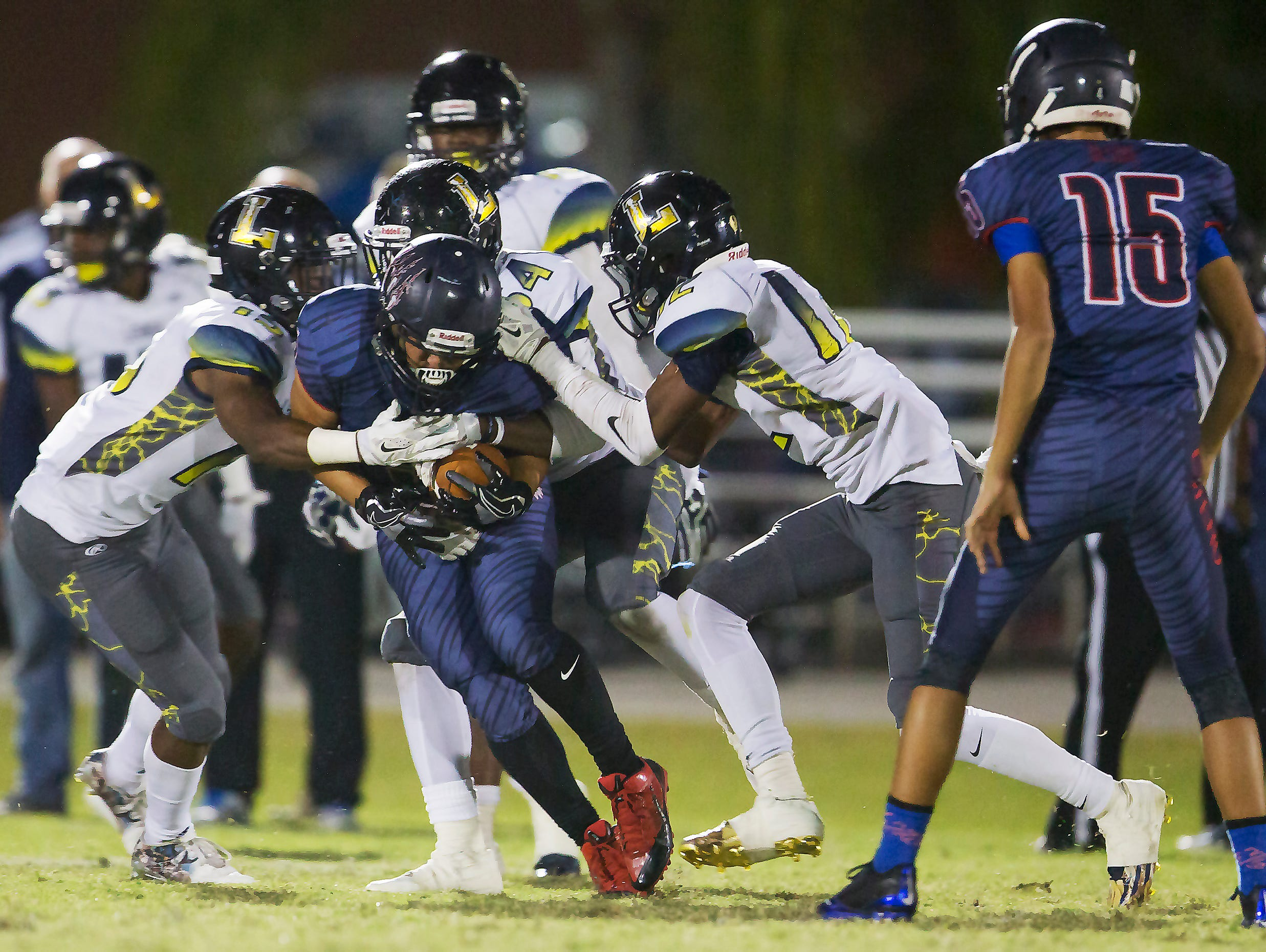 Lehigh Senior High School defenders tackle Estero's Justin Lopez for a loss during second quarter play on Friday at Estero High School.
