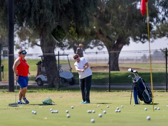 Kate Morales-O'neil, left, gives a lesson to Carol Olincy at Valley Oaks Golf Course on Tuesday.